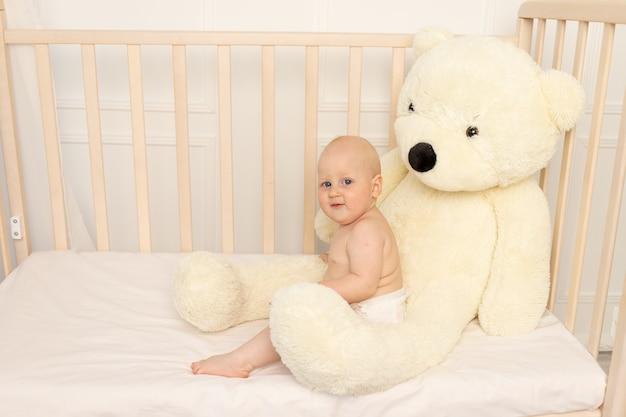 Chłopiec siedzi w pieluchach w łóżeczku z dużym misiem w przedszkolu