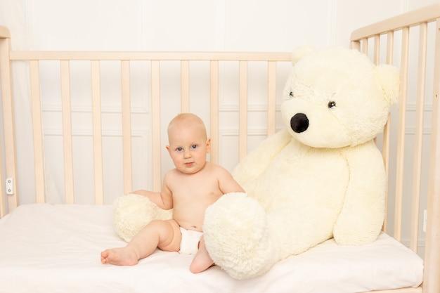 Chłopiec siedzi w pieluchach w łóżeczku z misiem