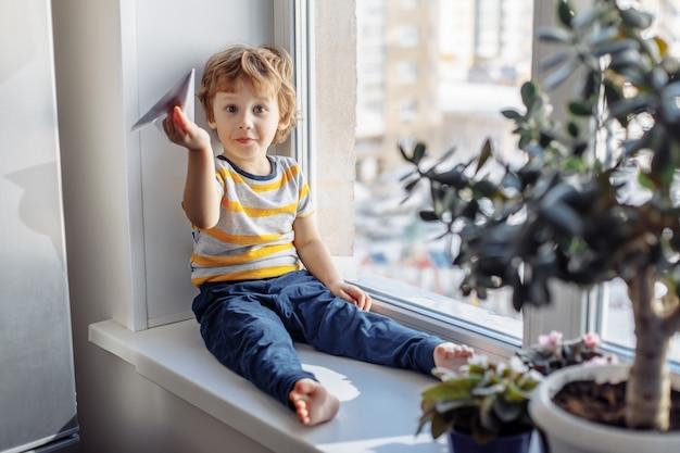 Chłopiec siedzi w pobliżu okna. koncepcja pobytu w domu