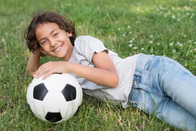 Chłopiec siedzi w trawie z piłki nożnej