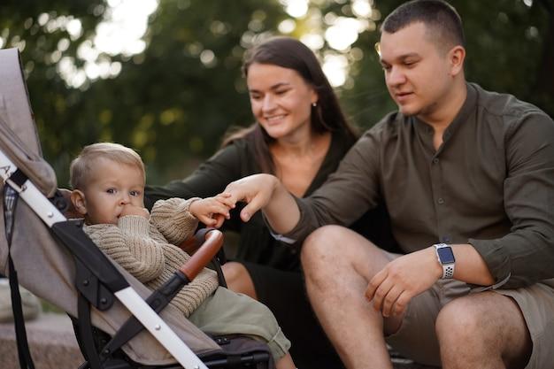 Chłopiec siedzi w wózku jego młodzi rodzice na tle, siedząc przy kamiennej balustradzie looki