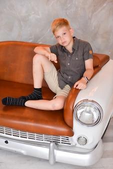 Chłopiec siedzi we wnętrzu studia na krześle w postaci samochodu retro. kreatywne meble w stylu vintage