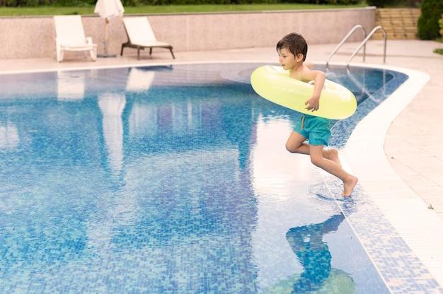 Chłopiec skacze w basenie z pływakiem