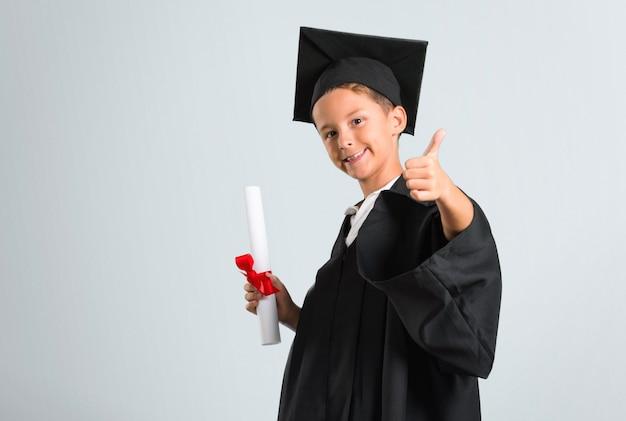 Chłopiec skalowanie daje aprobata gestowi i ono uśmiecha się na popielatym tle