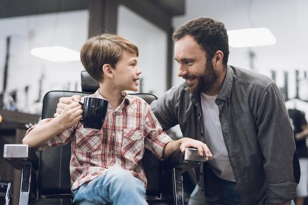 Chłopiec słucha dorosłego mężczyzny siedzącego w sklepie fryzjerskim.