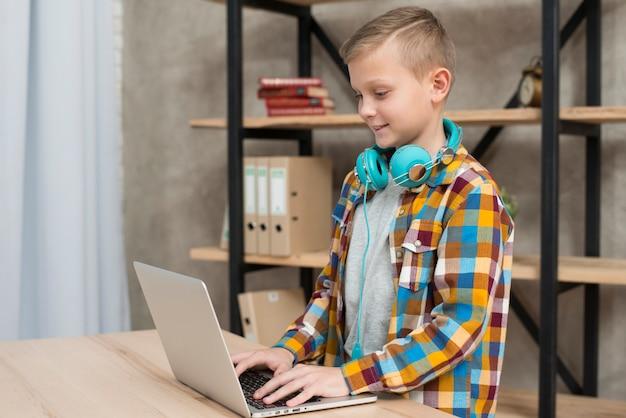 Chłopiec słucha muzyka na laptopie