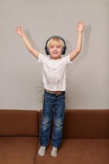 Chłopiec słucha muzyki i tańczy z podniesionymi rękami