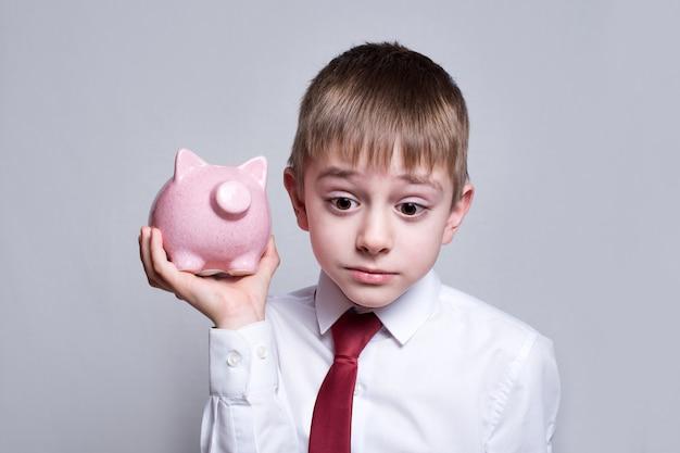 Chłopiec słucha uważnie różowej skarbonki. biznes . lekki