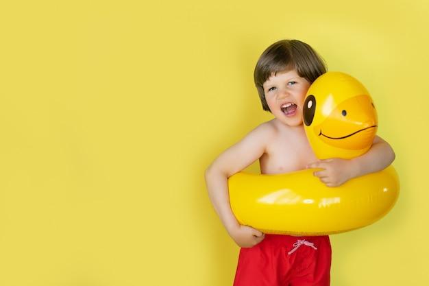 Chłopiec śmia się będący ubranym kaczka basenu nadmuchiwanego pławika na żółtym tle z kopii przestrzenią