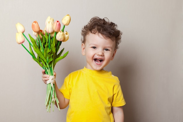Chłopiec śmia się wśród różowych tulipanów
