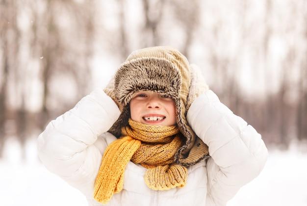 Chłopiec śmieje się i bawi się zimą w parku