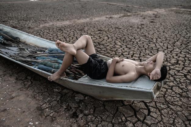 Chłopiec spał na łodzi rybackiej i położył ręce na czole na suchej podłodze, globalne ocieplenie
