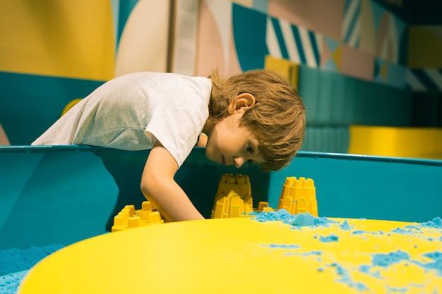 Chłopiec spędza czas w centrum zabaw dla dzieci. rozwój umiejętności motorycznych. nowoczesne gry edukacyjne. kreatywność i samorealizacja. łagodzenie stresu i napięcia. terapia sztuką.