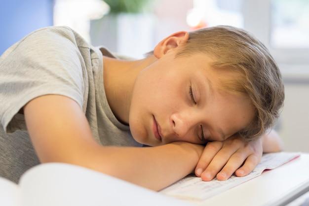 Chłopiec śpi na książkach