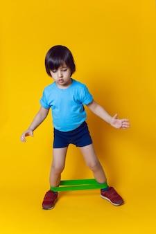 Chłopiec-sportowiec uprawia gimnastykę z gumką w klubie sportowym na żółtej ścianie