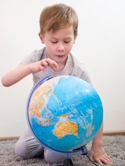Chłopiec sprawdza ziemską kulę ziemską