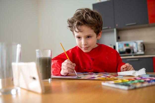 Chłopiec starannie rysuje, korzystając z lekcji online na odległość