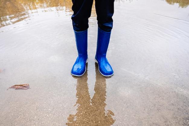 Chłopiec stoi na kałuży z wodą na dzień ulicie z błękitne wody butami.