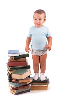 Chłopiec stoi na stosie książek do edukacyjnego portretu - na białym tle nad białą powierzchnią
