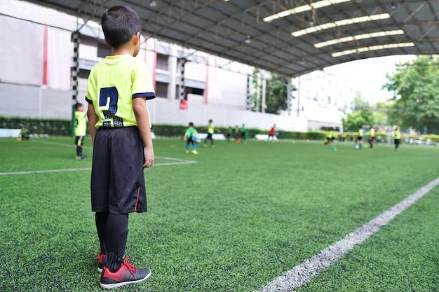 Chłopiec stoi na treningu piłkarskim juniorów.