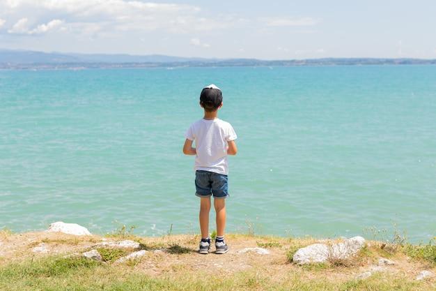 Chłopiec stoi na wybrzeżu jeziora, słoneczny dzień. zdrowy wypoczynek. lato. spokój. natura. widok panoramiczny. niebieska czysta woda. krajobraz. pocztówka. podróżować. letnie rodzinne wakacje.