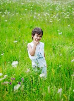 Chłopiec stoi na zielonej łące