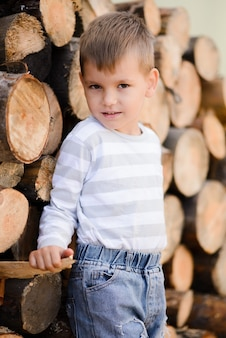 Chłopiec stoi obok drewnianych bali i uśmiecha się patrząc w kamerę