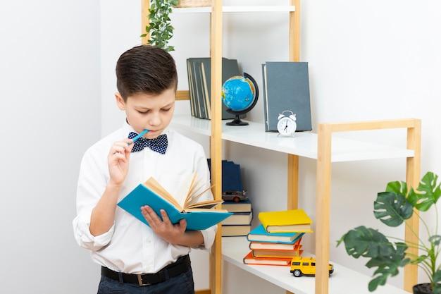 Chłopiec stoi podczas czytania