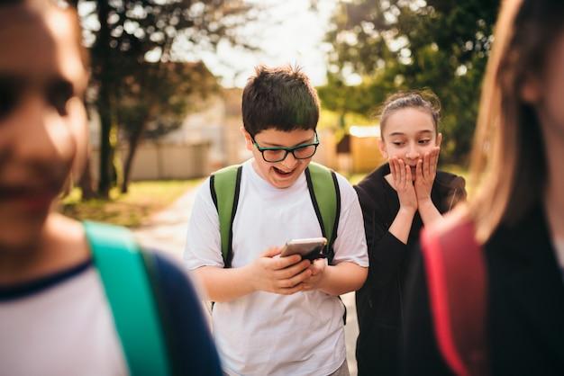 Chłopiec stoi przy szkolnym cybernękaniem