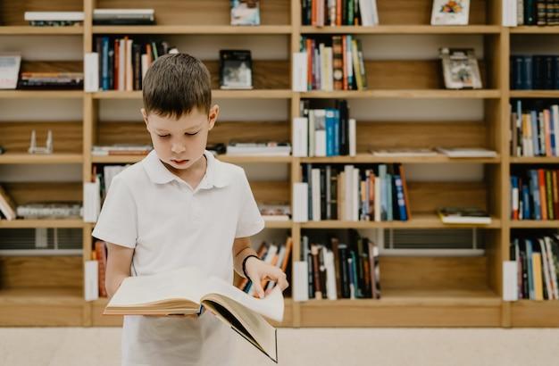 Chłopiec stoi w bibliotece i czyta książkę stojąc. przygotowanie do pracy domowej. chłopiec uwielbia czytać. wolna przestrzeń w szkole. nauka pozalekcyjna.