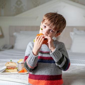 Chłopiec stoi wyśmienicie hamburger w pulowerze w sypialni i je.