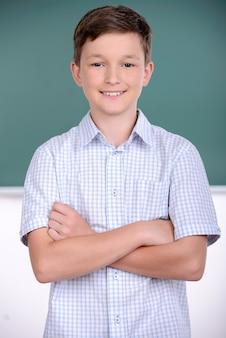 Chłopiec stoi z ręką w szkole.