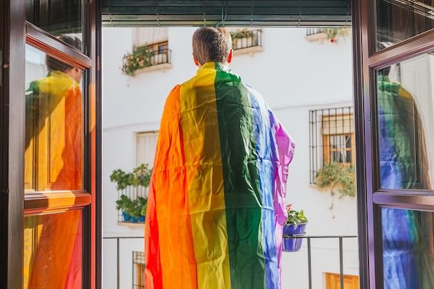 Chłopiec stojący na balkonie od strony ulicy z tęczową flagą na ramionach. lgtbi, wesoły