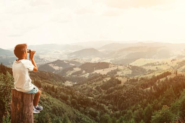 Chłopiec stojący na pniu w górach latem o zachodzie słońca i podziwiając widok na przyrodę