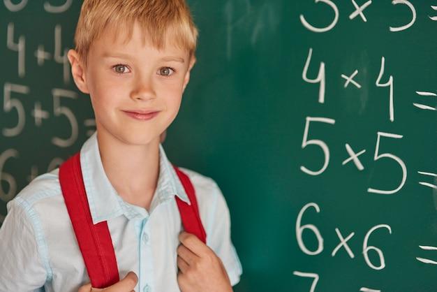 Chłopiec stojący obok tablicy