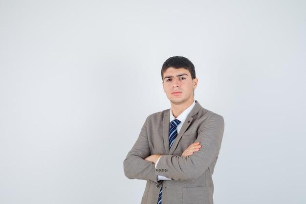 Chłopiec stojący rękami skrzyżowanymi w formalnym garniturze i patrząc pewnie, z przodu.