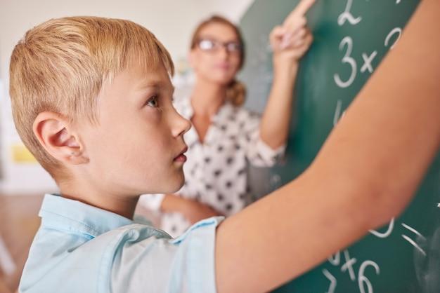 Chłopiec student robi problem matematyczny na tablicy