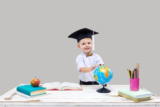 Chłopiec studiuje podczas gdy będący ubranym skalowanie na szarej odosobnionej ścianie