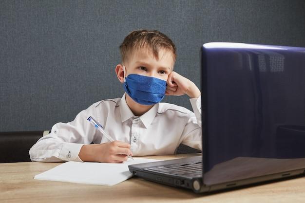 Chłopiec studiuje pracę domową matematykę podczas lekcji online w domu