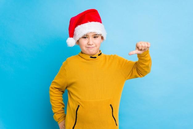 Chłopiec świętuje boże narodzenie dzień jest ubranym santa kapelusz odizolowywającego pokazywać niechęć gest, kciuki zestrzela. pojęcie nieporozumienia.