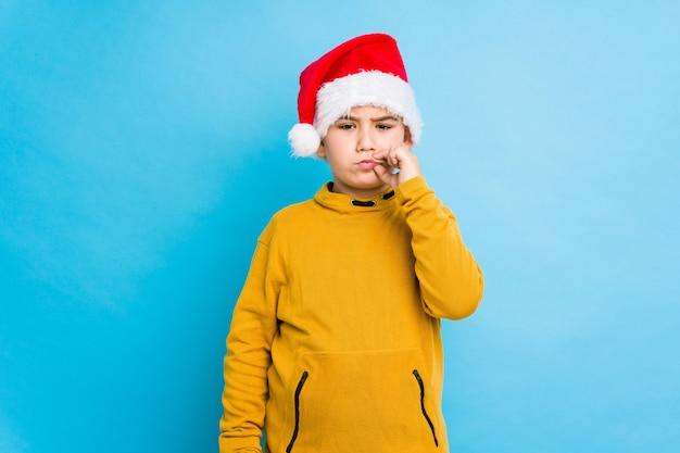 Chłopiec świętuje boże narodzenie dzień jest ubranym santa kapelusz odizolowywającego z palcami na wargach utrzymuje sekret.