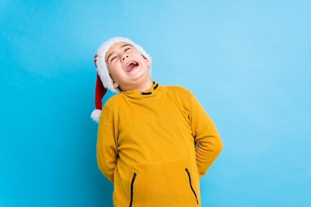 Chłopiec świętuje boże narodzenie dzień jest ubranym santa kapelusz odizolowywał zrelaksowanego i szczęśliwego śmiać się, szyja rozciągał pokazywać zęby.