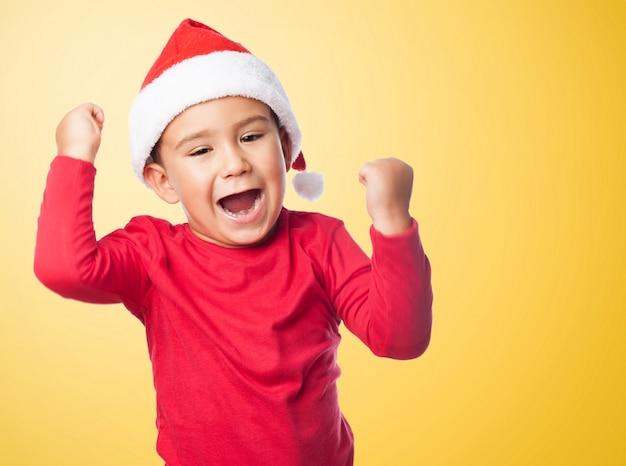 Chłopiec świętuje swoje zwycięstwo z pomarańczowym tle