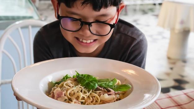 Chłopiec szczęśliwy jedzenie spaghetti carbonara przepis