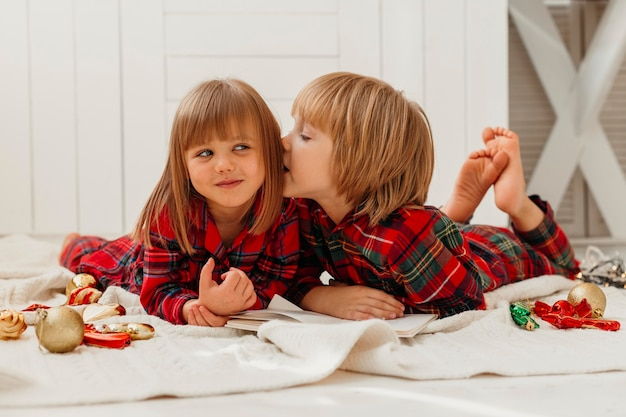 Chłopiec szepczący coś do swojej siostry