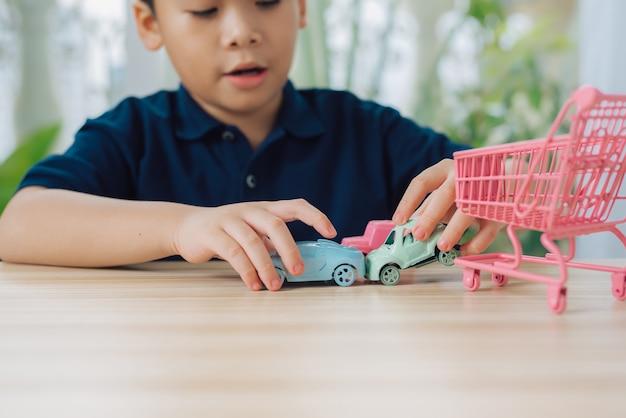 Chłopiec szkoły bawi się samochodzikiem na stole w domu.