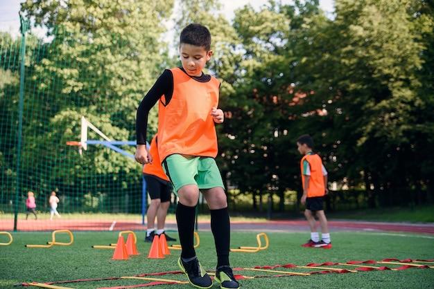 Chłopiec szkoły działa ćwiczenia drabinowe na murawie podczas treningu piłki nożnej