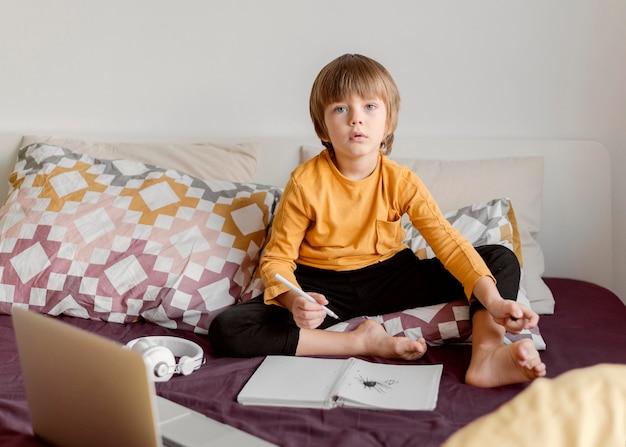 Chłopiec szkoły siedzi w łóżku widok z przodu