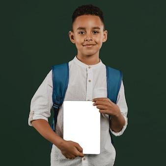 Chłopiec szkoły trzyma notatnik przestrzeni kopii