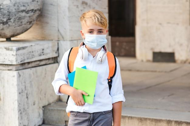 Chłopiec szkoły trzymając notebooki na sobie maskę